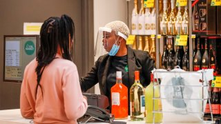 An employee wearing a face mask rings up a customer's alcohol purchase at the Local Market Foods store in Chicago, Illinois, on April 8, 2020, during the coronavirus outbreak.