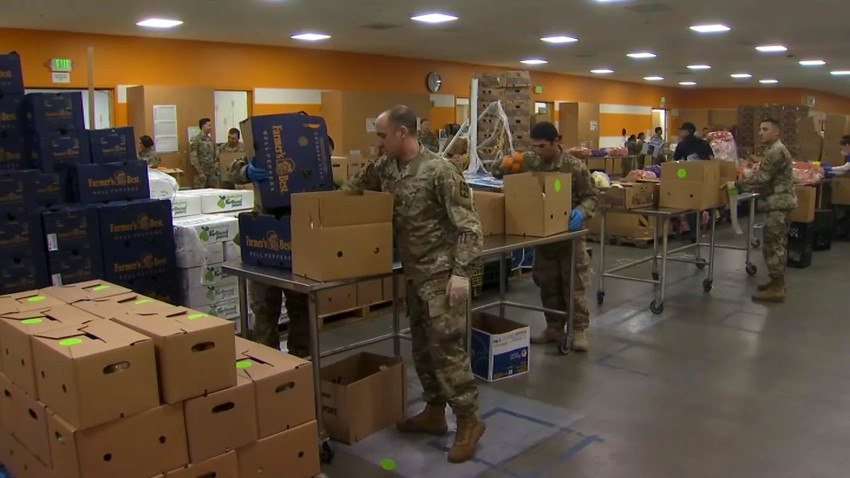 Members of the National Guard fill food boxes at Second Harvest Food Bank.