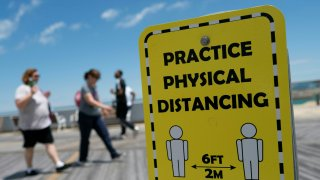 People walk past a sign advising about social distancing.