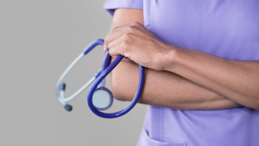 Female doctor holding stethoscope, arms folded.