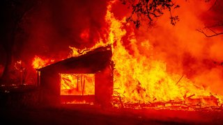 In this Sept. 27, 2020, file photo, a building burns during the Glass fire in St. Helena, California.