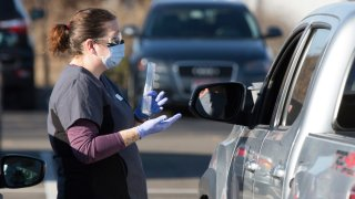 An employee gives instructions for self-administering a COVID-19 test in the parking lot at Primary Health Medical Group's clinic in Boise, Idaho, Tuesday, Nov. 24, 2020. The urgent-care clinic revamped into a facility for coronavirus patients as infections and deaths surge in Idaho and nationwide. Some 1,000 people have died due to COVID-19, and infections this week surpassed 100,000.