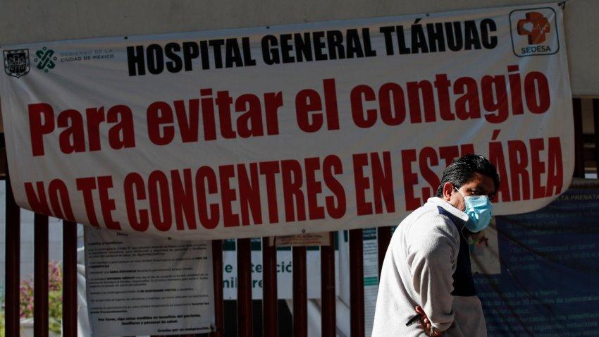 Hombre camina frente un aviso de alerta de contagio en Ciudad de México