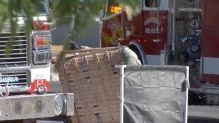 Fotografía de partes de dos vehículos de bomberos entre los que está la canastilla de un globo aerostáticos accidenteado.