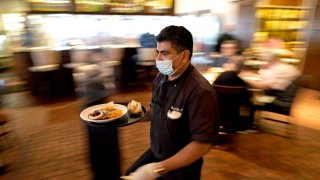 Marcelino Flores wears a face mask as he delivers food to a table at Picos restauran